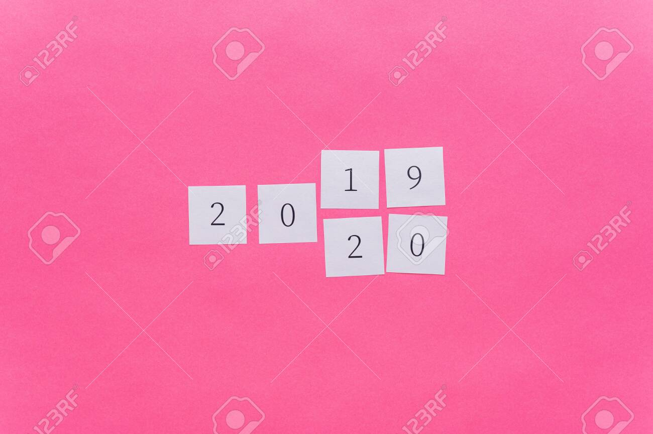 2019 written on white note papers changing the last two digits to 2020 in a conceptual image of the coming new year. Over pink background with copy space. - 134017664