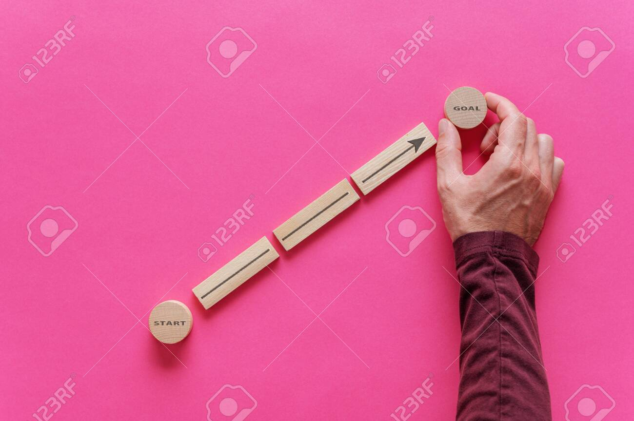 Male hand placing wooden pegs and circles to form a diagram with arrow pointing from word Start to Goal in a conceptual image of personal aspirations. Over pink background. - 134017716