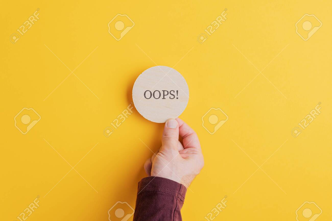 Male hand placing wooden cut circle with an Oops sign on it on bright yellow background. - 134018445
