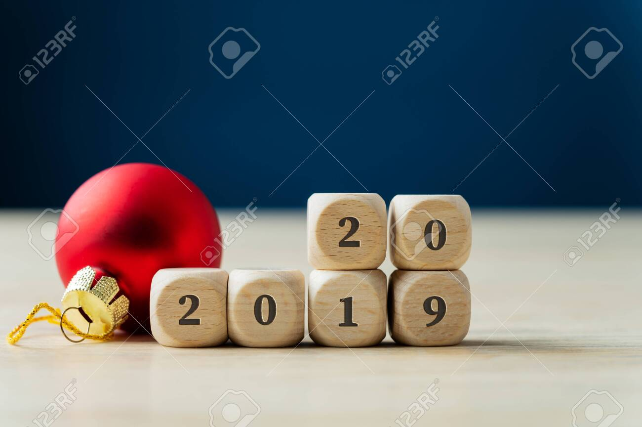 Red holiday bauble next to a 2019 sign on wooden dices with number 20 already on top. - 135881517