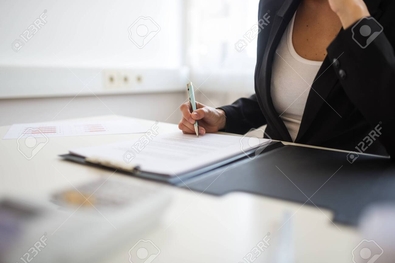 Closeup view of businesswoman sitting at her desk signing a document or contract in a folder. - 147874268