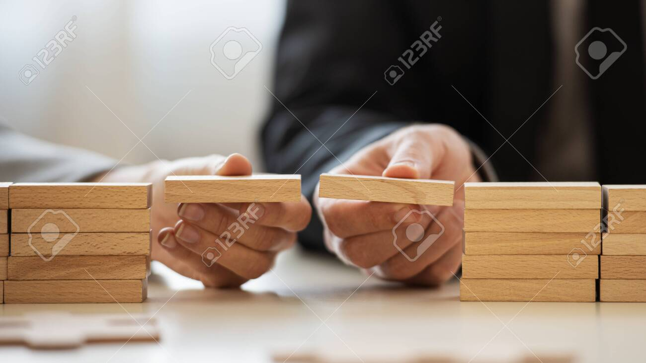 Closeup view of businessman and businesswoman making a bridge of wooden blocks between two stacks of them in a conceptual image of merger and cooperation. - 150068923