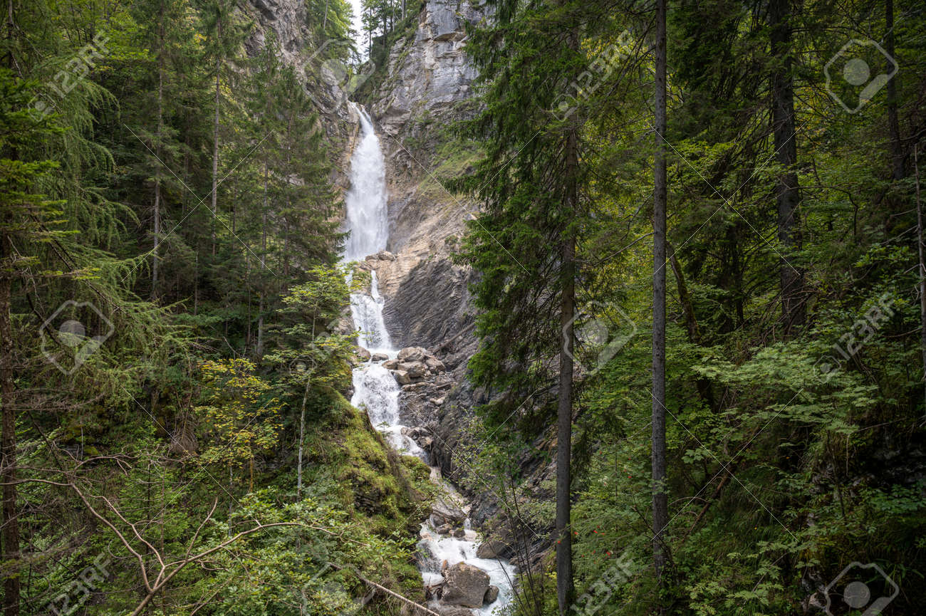 Beautiful waterfall falling down the rocks in green summer forest. - 169239309