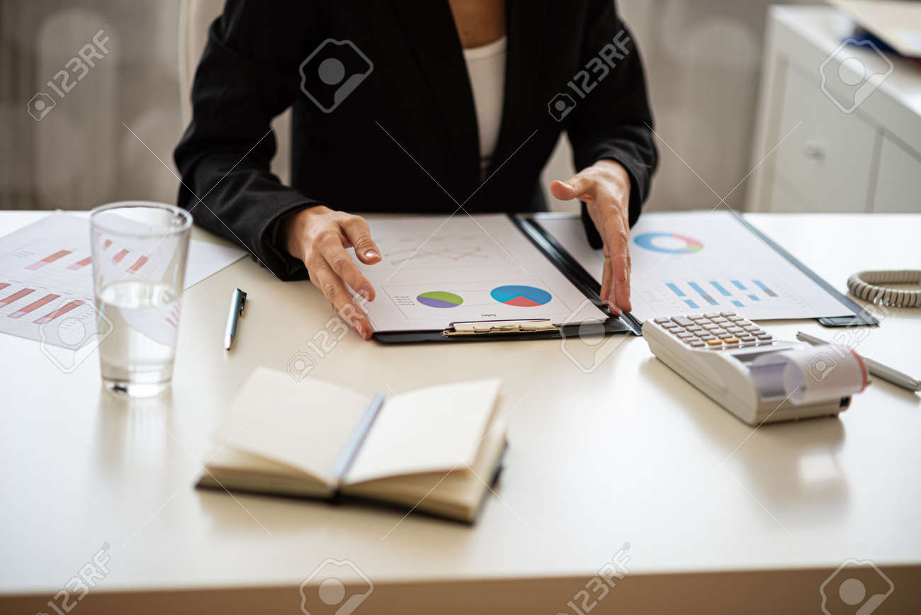 Businesswoman sitting at her desk working on financial report with graphs and charts. - 169239310