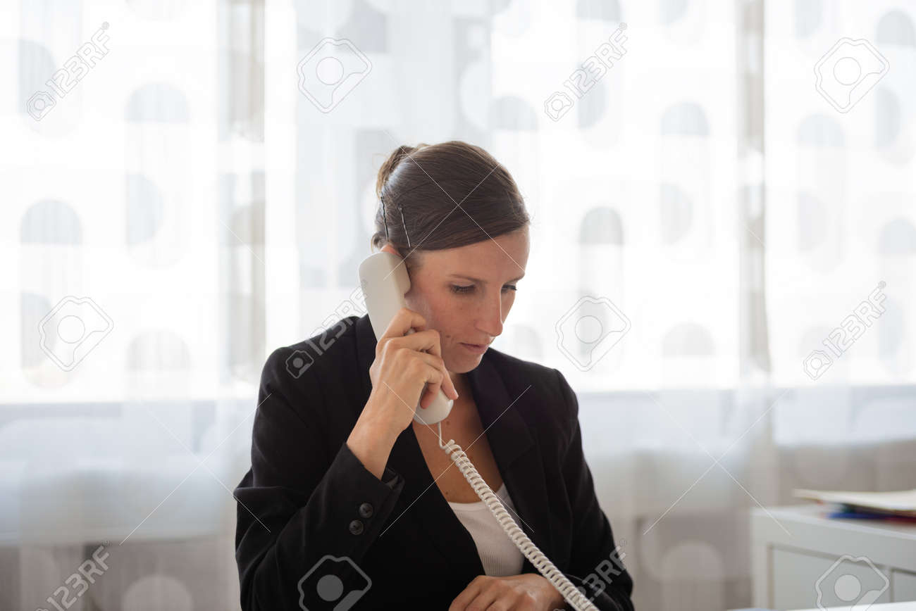 Young businesswoman, secretary, sitting ate her office desk talking on a white landline telephone. - 169239342