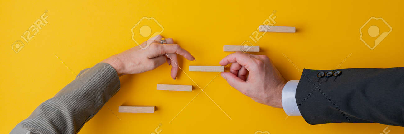 Hand of a businessman supporting a step in conceptual stairway for his female partner to walk her fingers upwards. Wide view image over yellow background. - 169239314