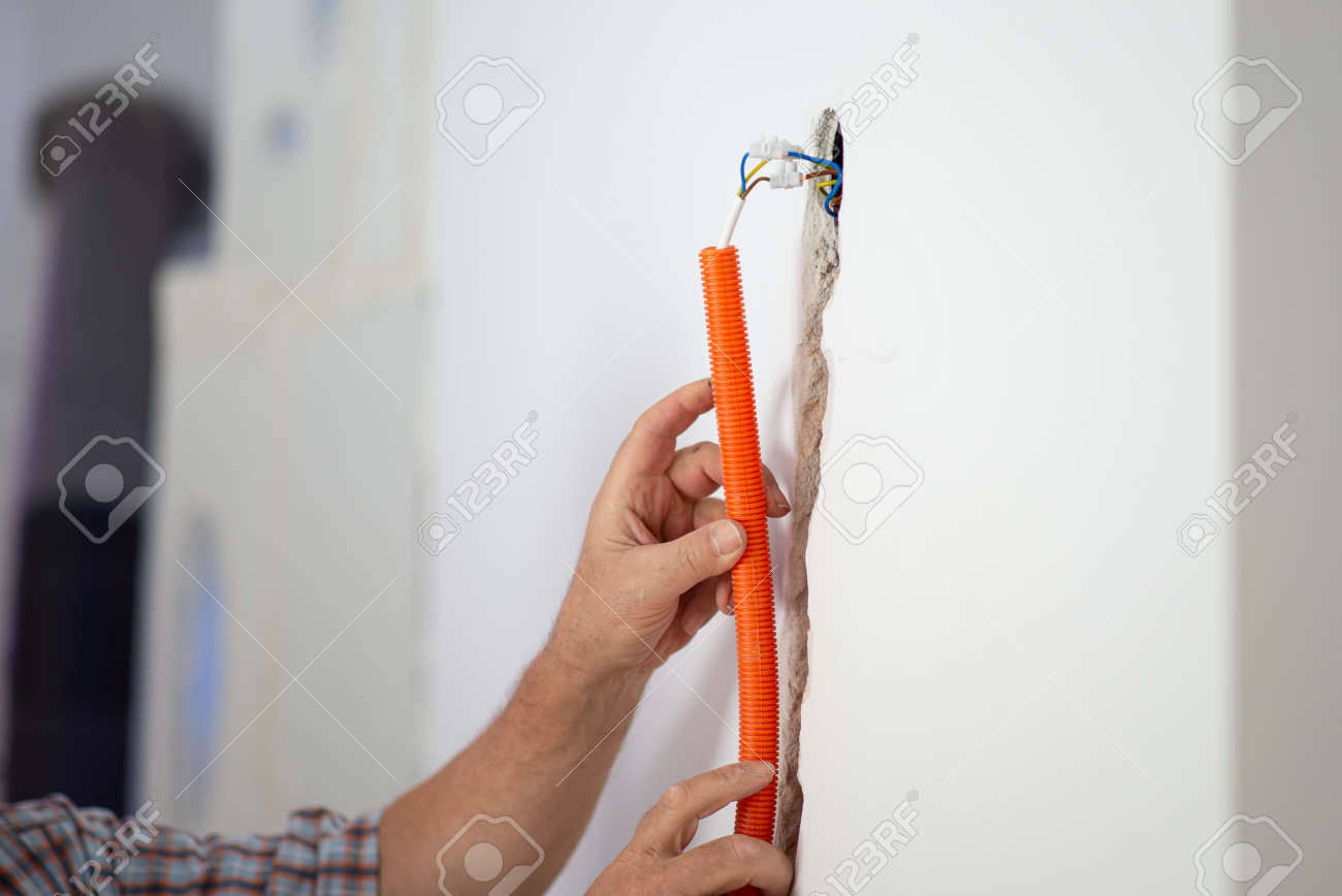 Closeup view of a workers hands positioning orange corrugated tube into a hole in a wall as a part of electrical installation. - 169239315
