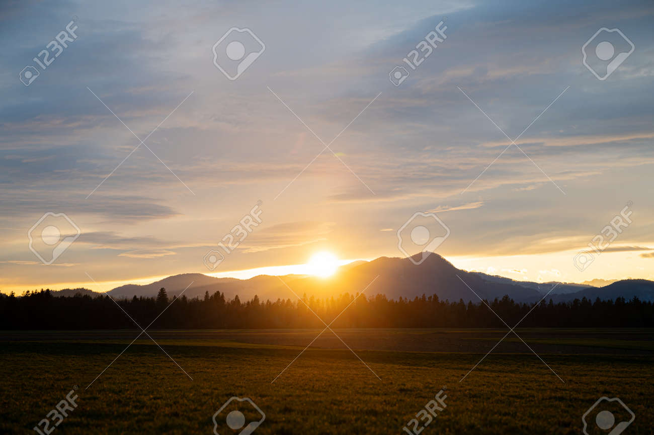 Beautiful sunset with the sun setting behind the distant hills with cloudy sky above. - 169239345