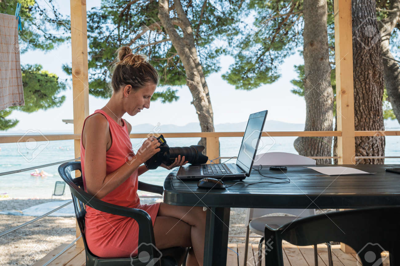 Young female photographer sitting on a porch by the sea transferring her photos from camera to laptop computer for further editing and processing. - 169239353