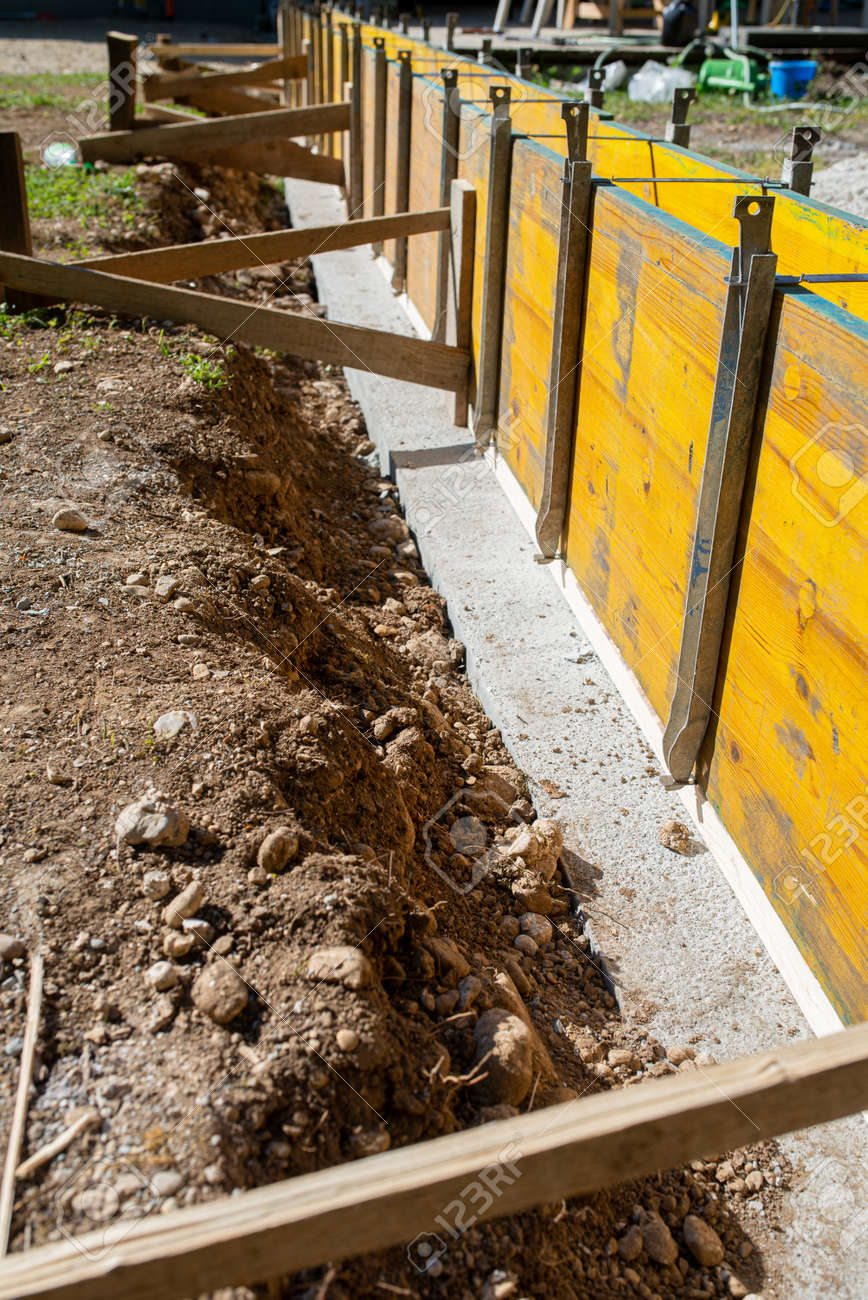 Construction site outside in backyard of a framework of wooden panels ready for cement to be poured in. - 169239356