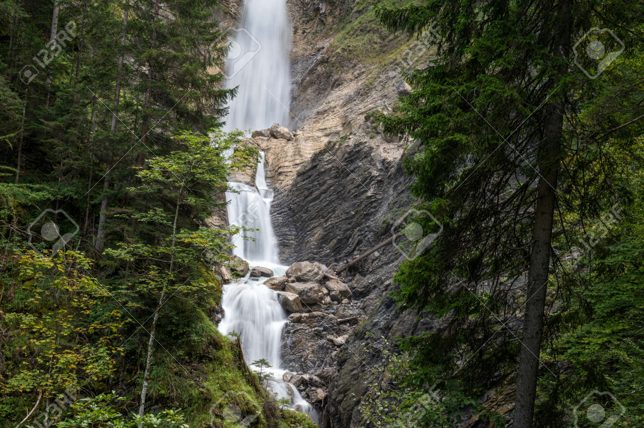 Long exposure image of a beautiful waterfall falling over the rocks in a green summer forest. - 169239357