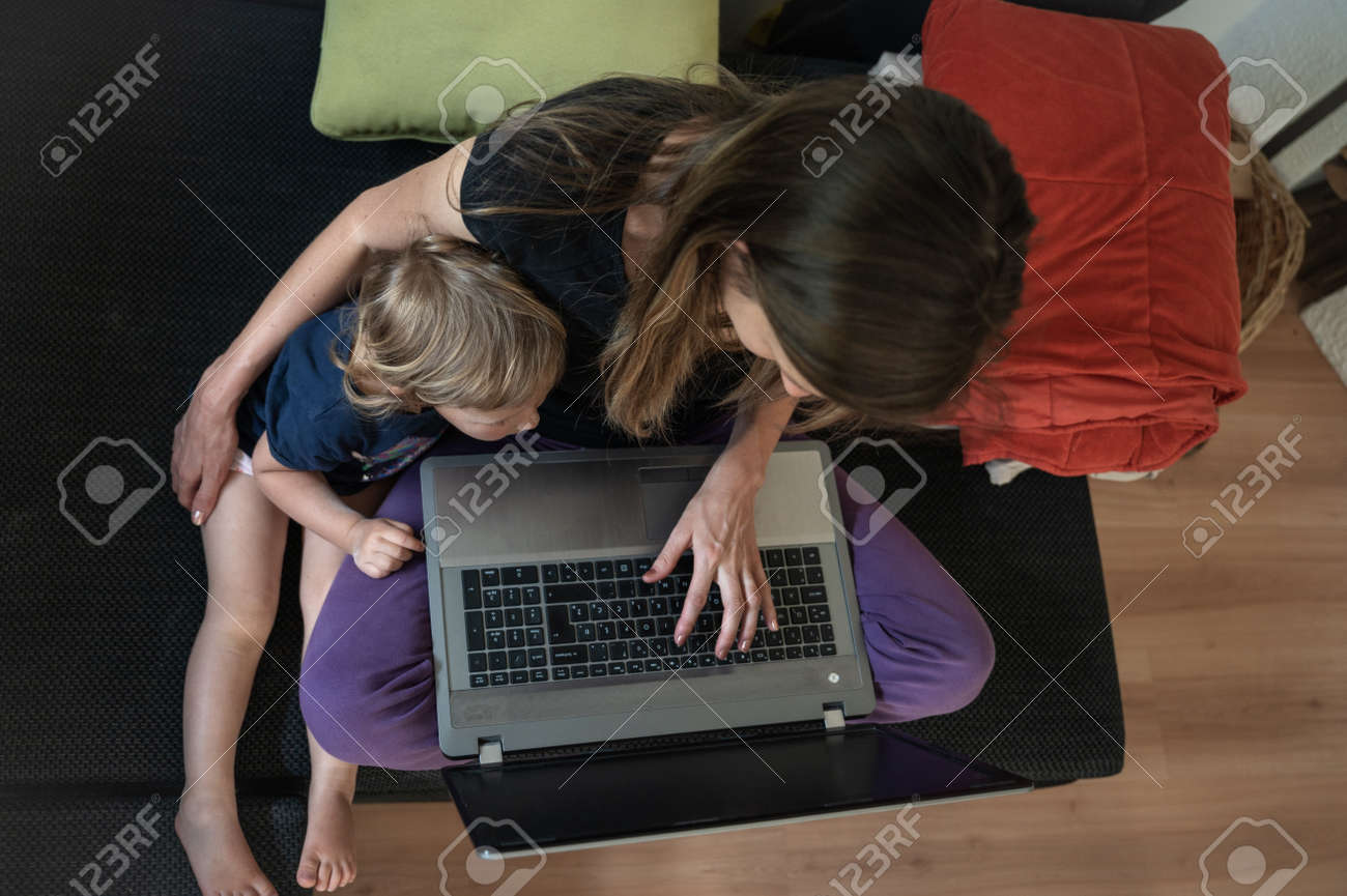 Top view of a young mother sitting on a sofa with laptop computer on her knees working with her toddler daughter cuddling next to her. - 169239360