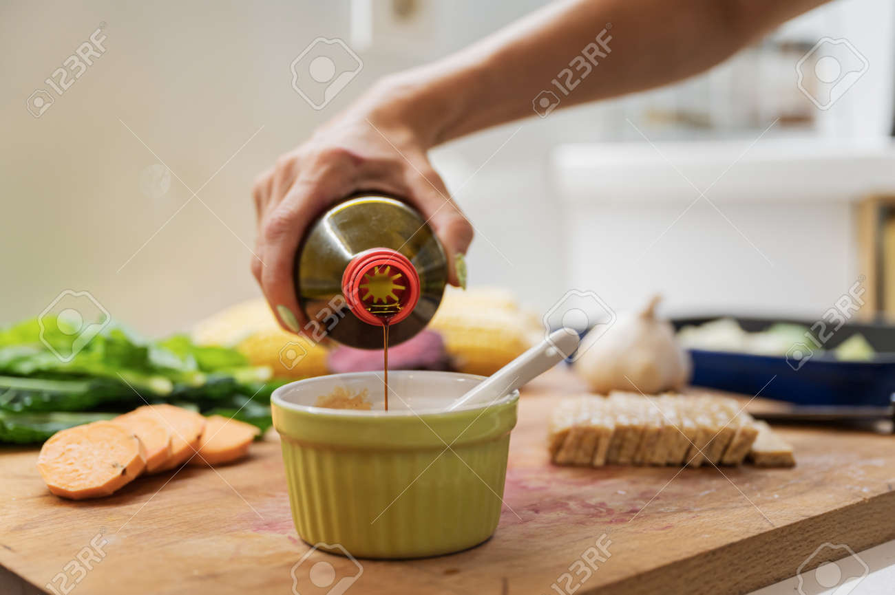 Closeup view of a woman pouring soya sauce into a cup to prepare a dip on wooden cutting board full of vegetables and vegan protein. - 169239394