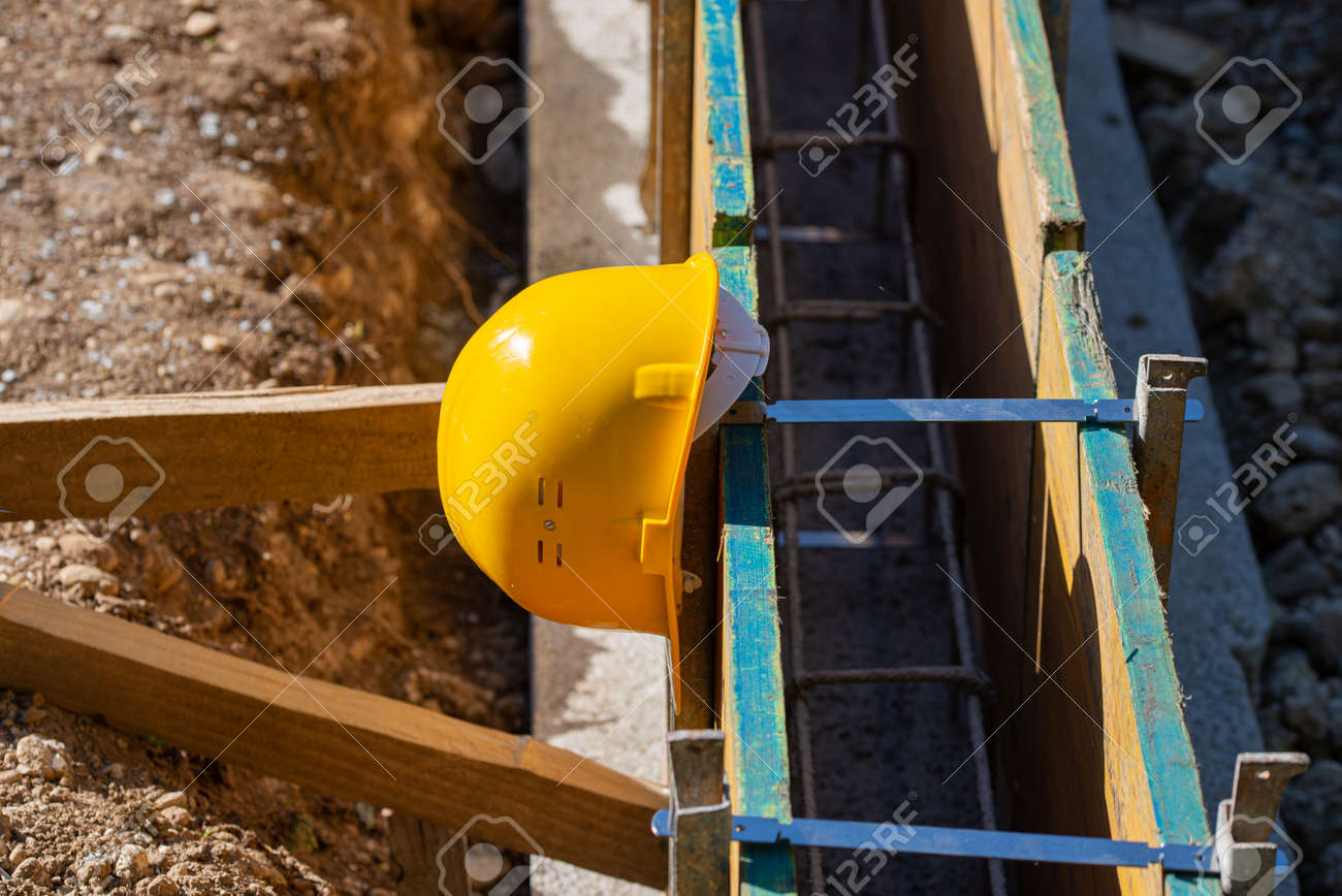 Yellow protective hardhat resting on a framework of wooden panels in a construction site. - 169239400