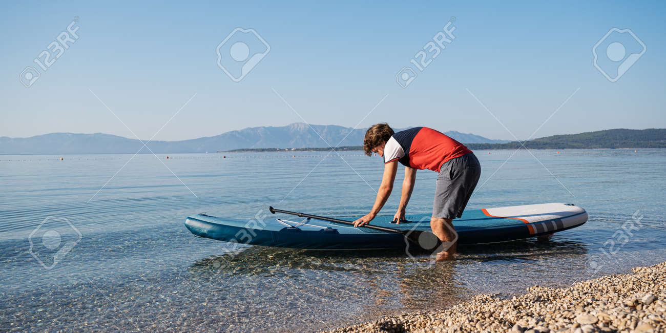 Young man about to go on a sup board to paddle on a calm morning sea water. - 169239398
