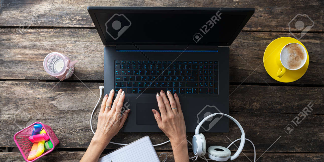 Top view of female student working on laptop computer with headphones, colorful markers and cup of coffee beside it on the table. - 169239401