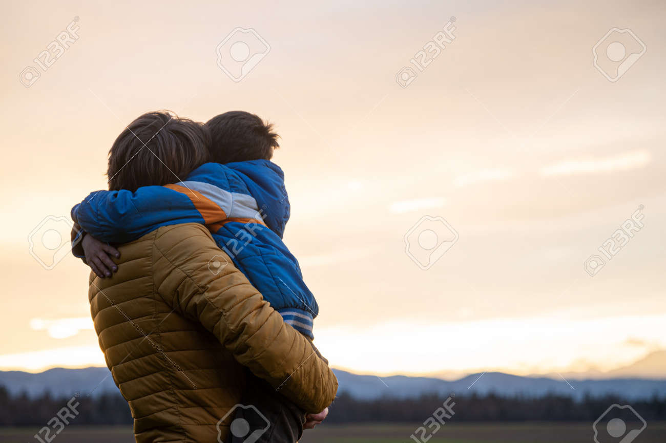 Beautiful moment between a father and son hugging each other while standing under beautiful evening sky enjoying nature and sunset. - 169239406