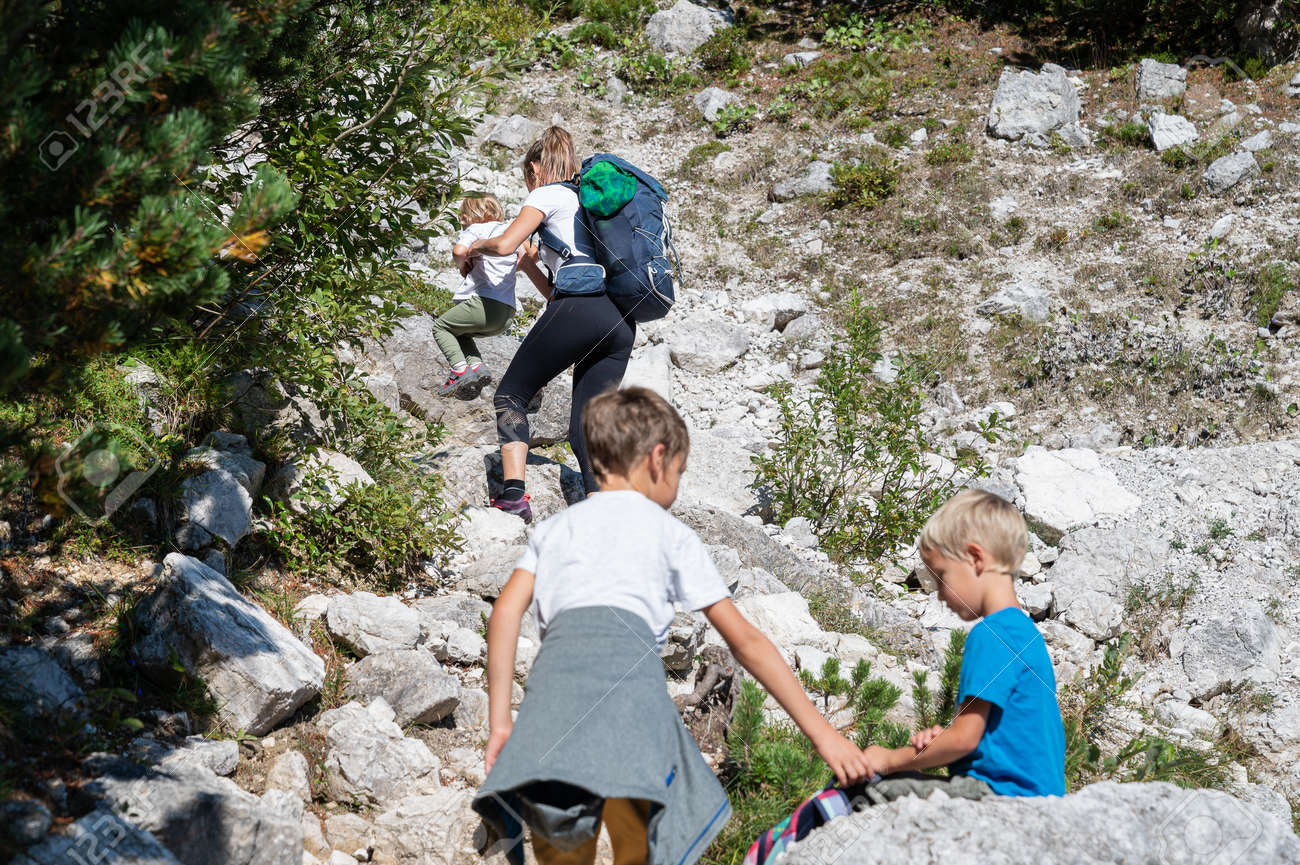 Young mother hiking in mountains with her three children. - 169239403