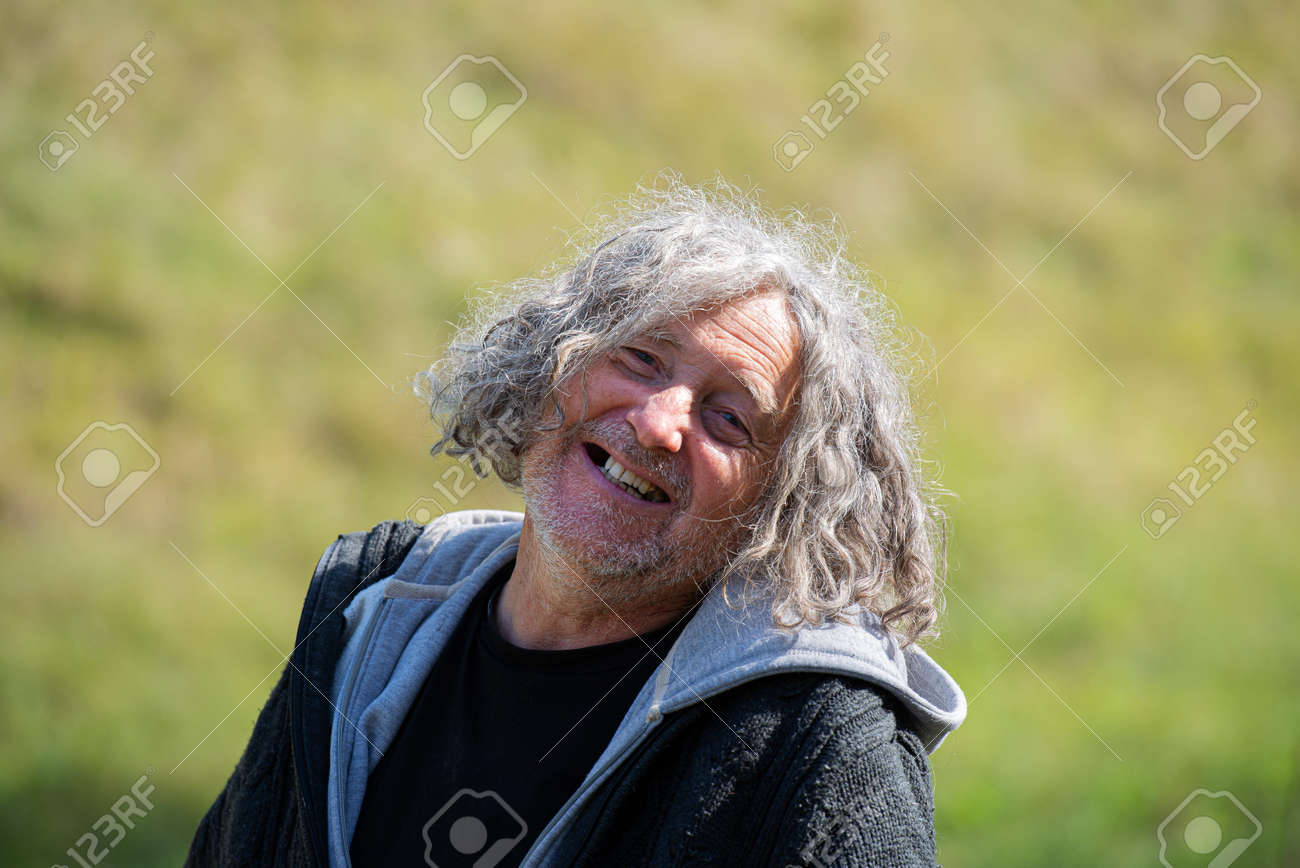 Portrait of a cheerful senior homeless man with a bright smile. - 169239405