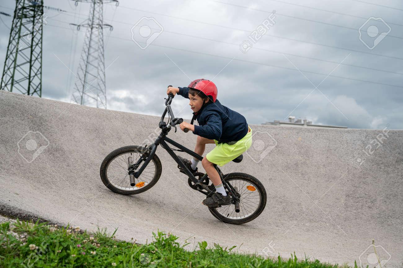 Young boy riding his bmx bike on a pumptrack. - 169239410