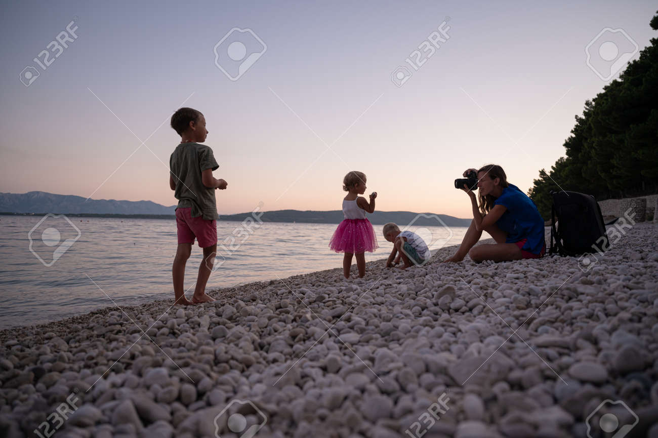 Young mother photographing her three children playing on pebble beach in a beautiful summer evening. - 169239412