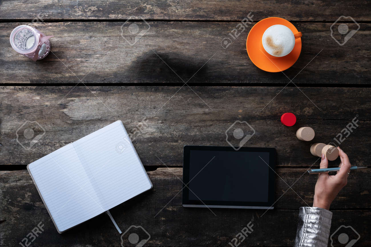 Top view of a woman working and brainstorming using digital tablet, notepad and stacking wooden blocks. - 171099187
