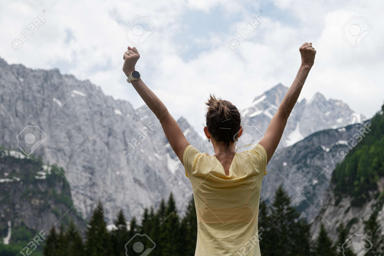 View from behind of a young woman standing under beautiful rocky mountains with her arms raised high. - 170456656