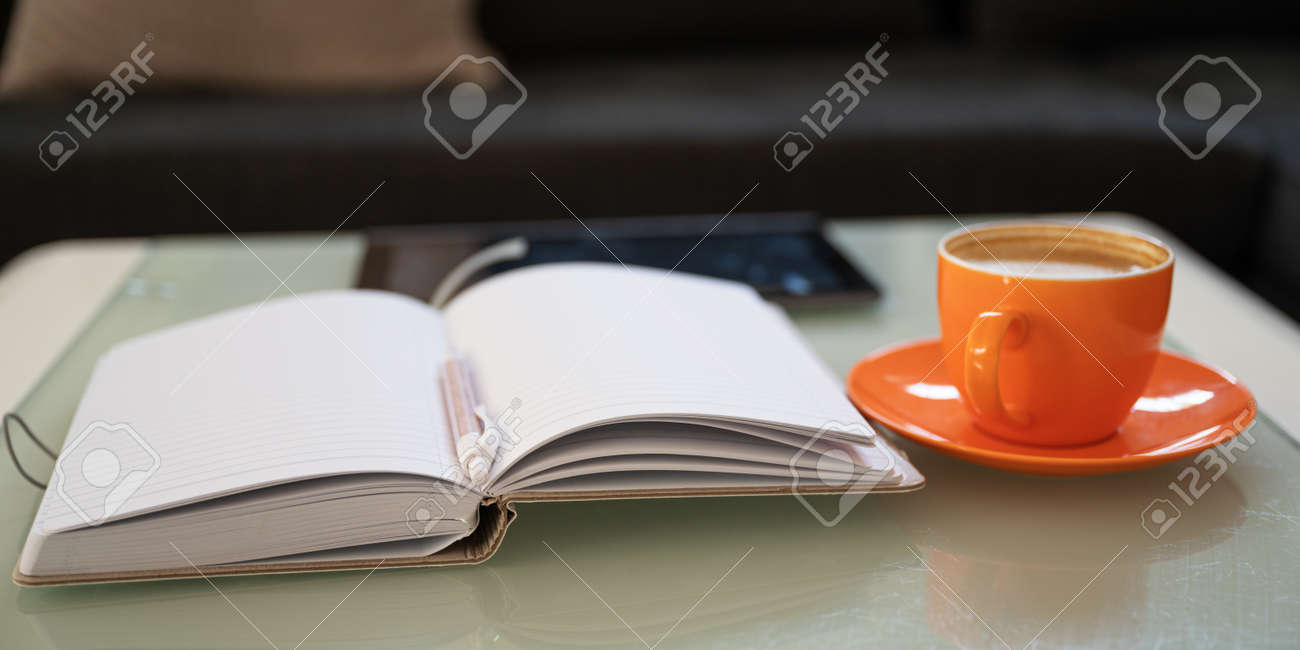 Open notepad with pen in the middle, cup of coffee and digital tablet lying on a coffe table in the living room. - 171334525