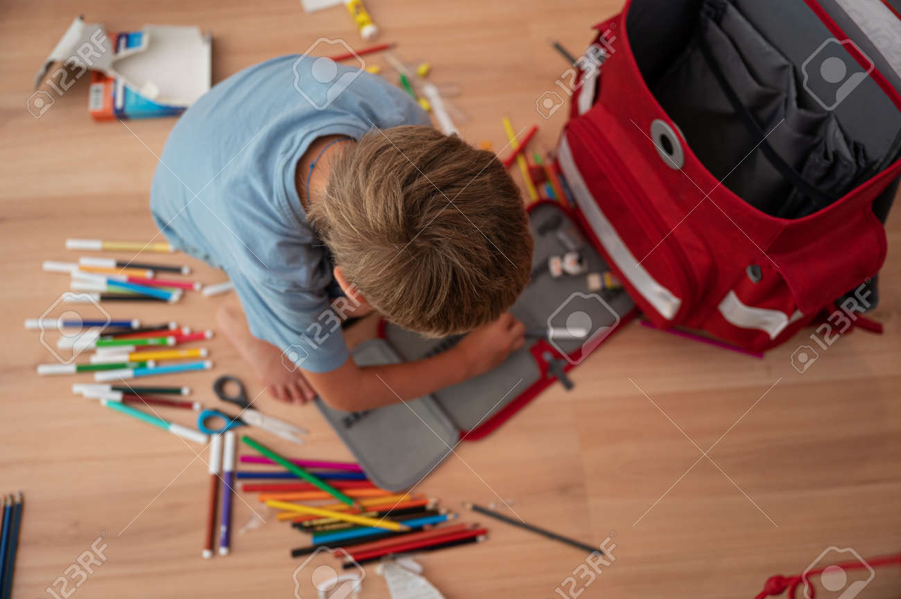 Back to school conceptual image - little boy sitting on the floor next to a school bag arranging his pencil case with color pencils. - 171940299