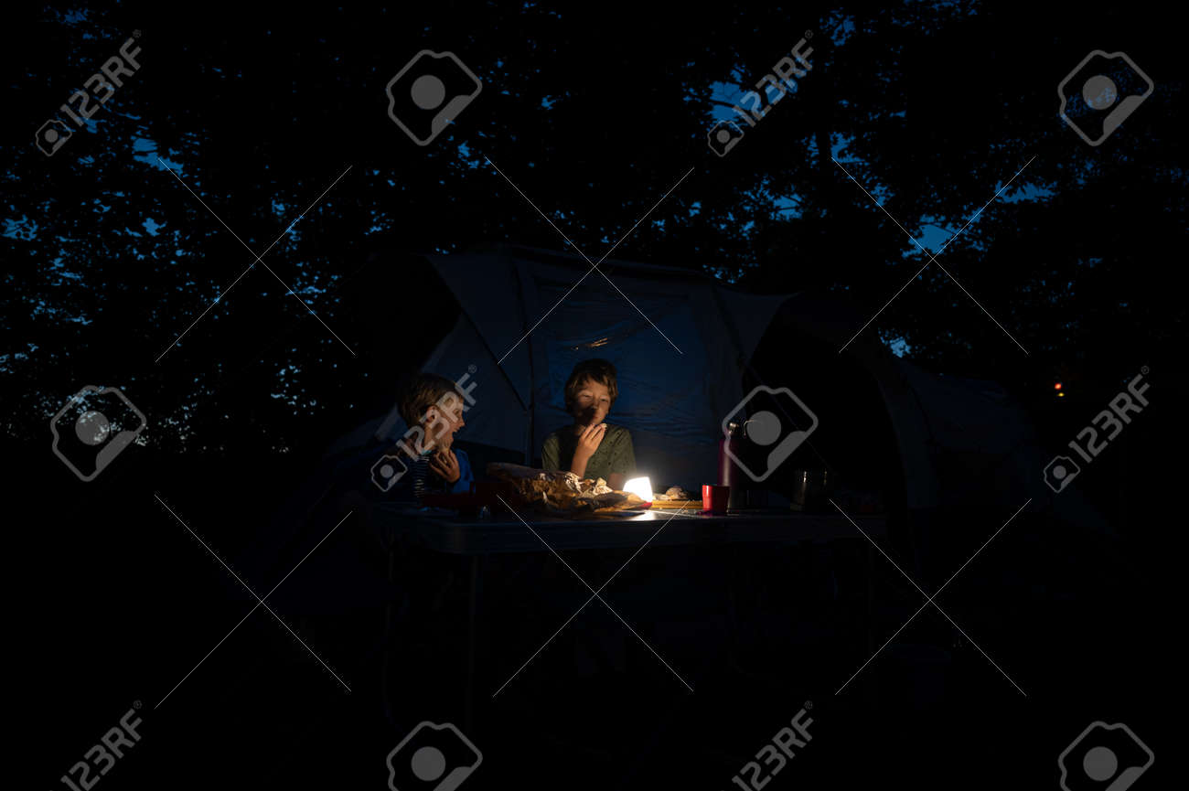 Two brothers sitting by their tent in a camping place eating dinner by a dimmed light. - 171940301