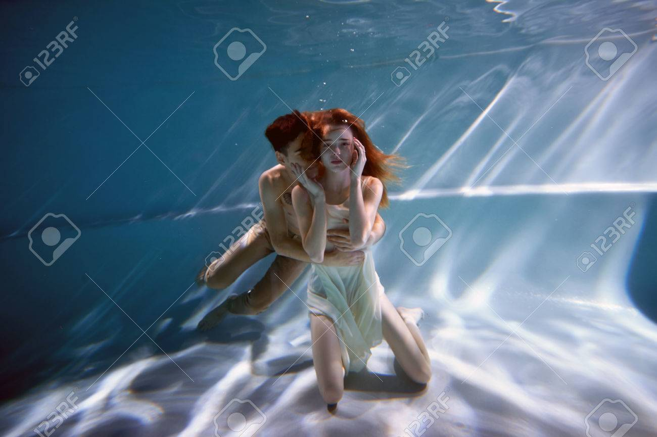 Underwater In The Pool With The Purest Water. Loving Couple Hugging. The  Feeling Of