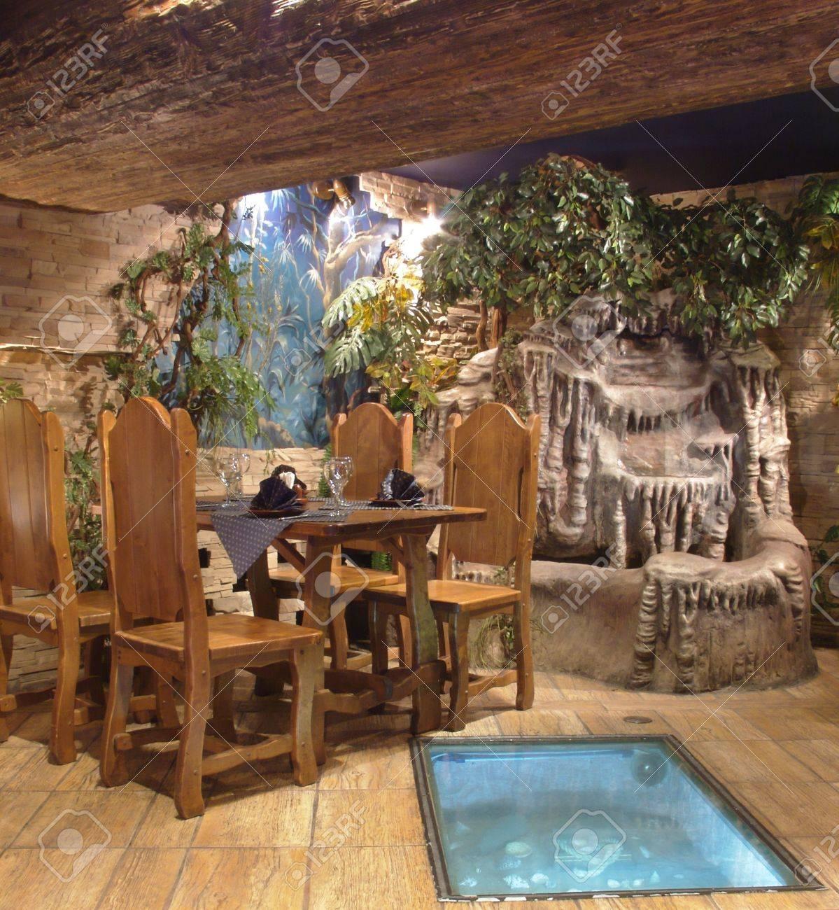 Foto De Archivo   Un Fragmento Del Interior. Mesa De Madera. Fuente  Colocado En Un Volcán. Fuente De Piedra. Decorado Con Vegetación Artificial.