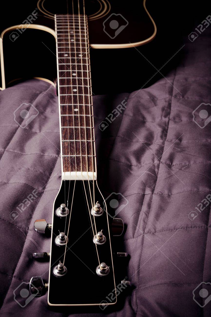 Black Shiny Acoustic Guitar On Bed Stock Photo Picture And Royalty