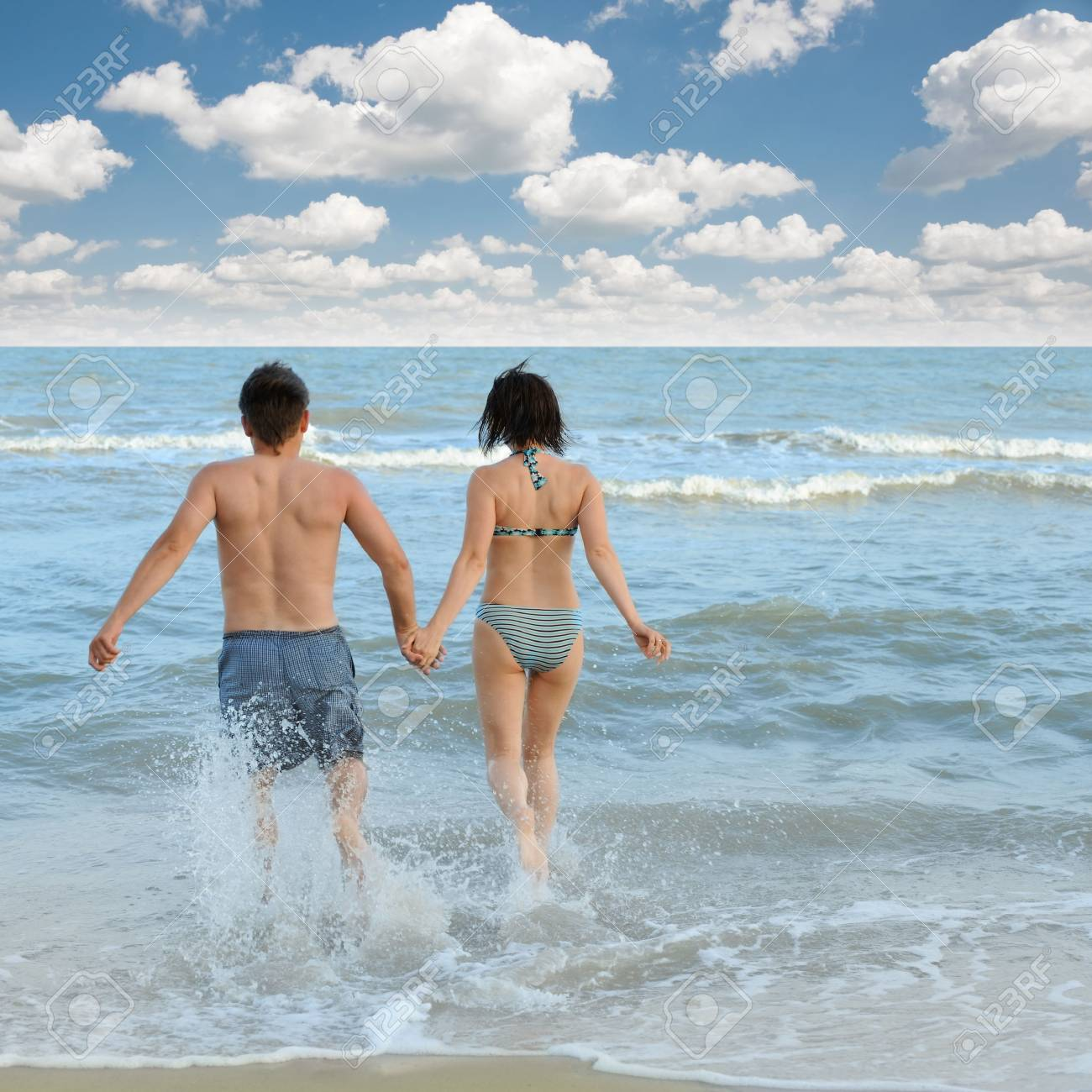 Pair on seacoast. The enamoured guy and the girl walking on coast Stock Photo - 5191474