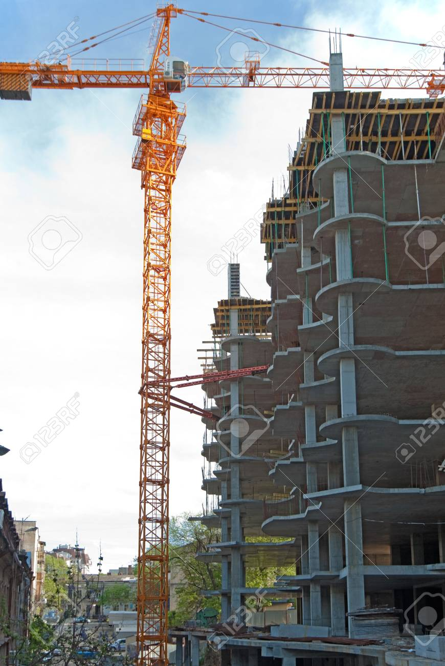 Construction of the building. The big elevating crane and not completed building Stock Photo - 5260165