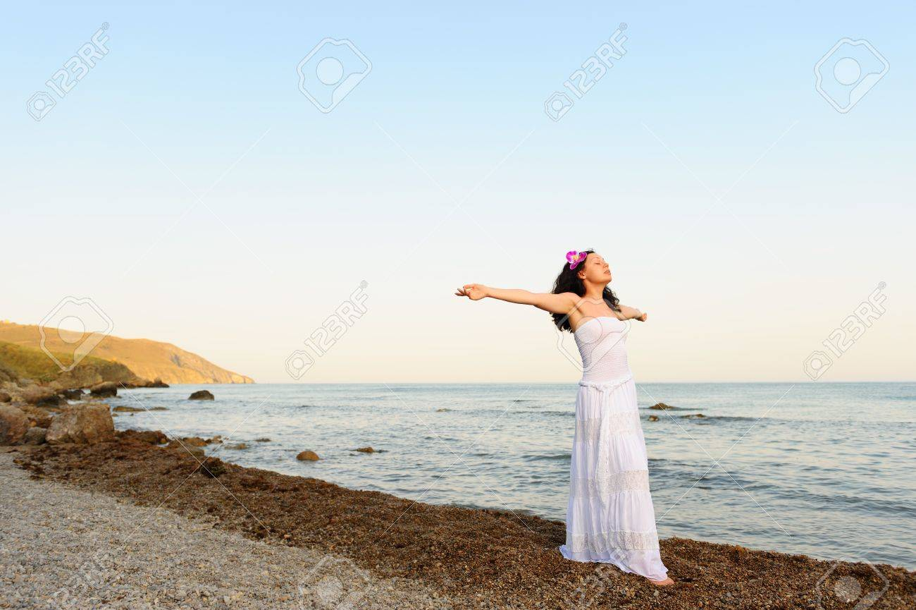 The woman in a white sundress on seacoast with open hands. A picturesque landscape Stock Photo - 10288533