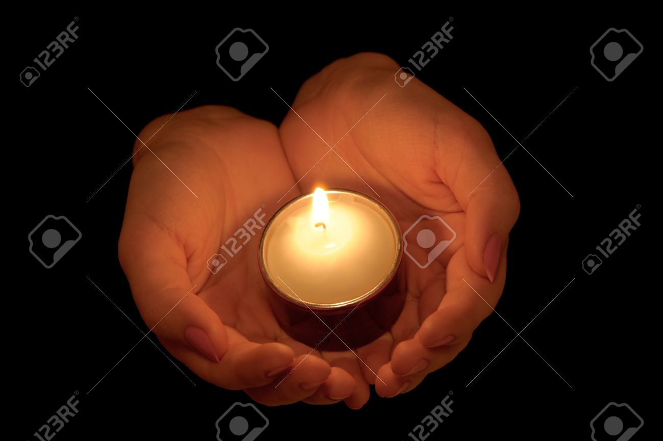Burning candle in female hands. A black background Stock Photo - 11061878