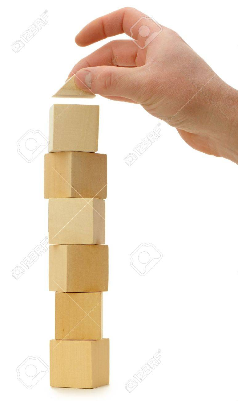The hand establishes a toy roof on wooden cubes. Isolated on white Stock Photo - 12700971