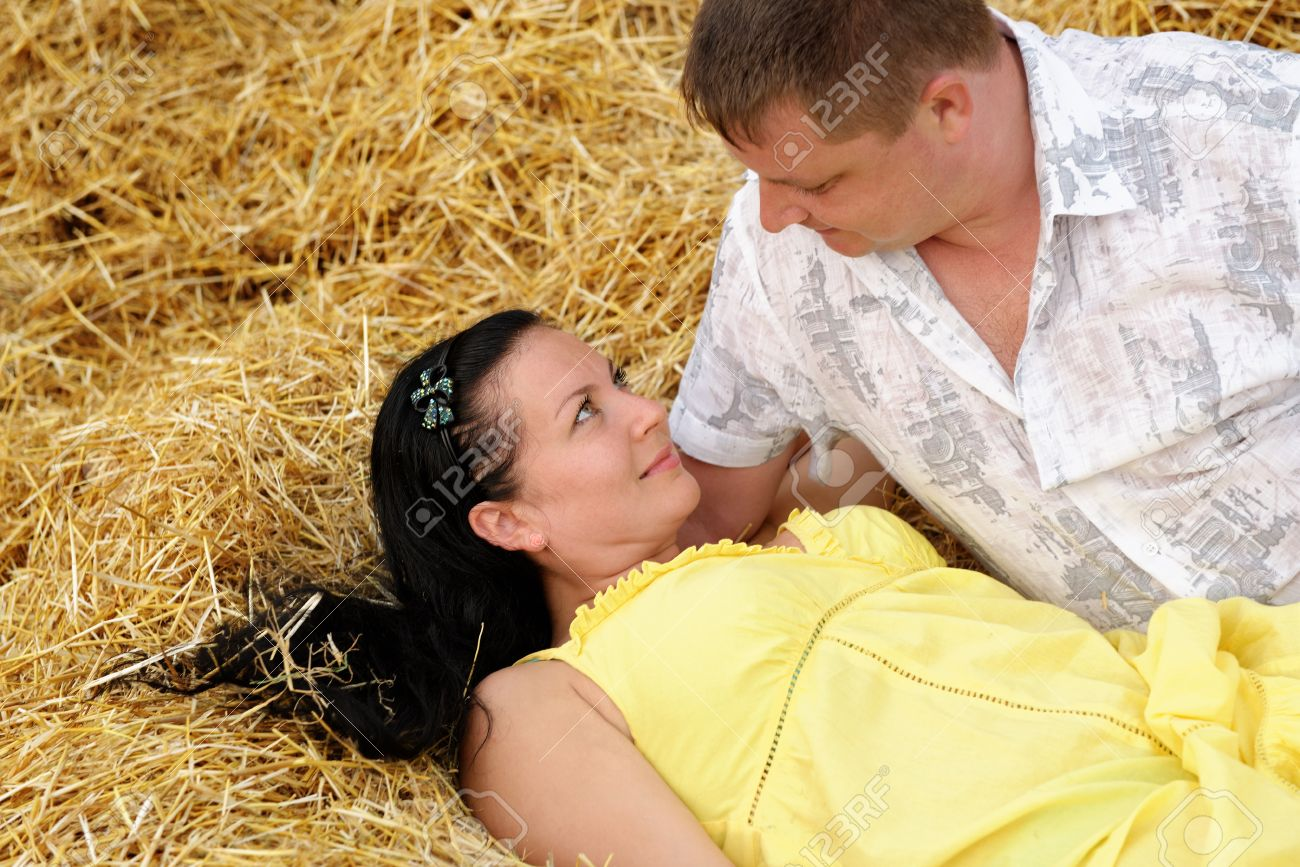 A couple in love at hay. Adult man and woman lie on the fresh hay Stock Photo - 14649521