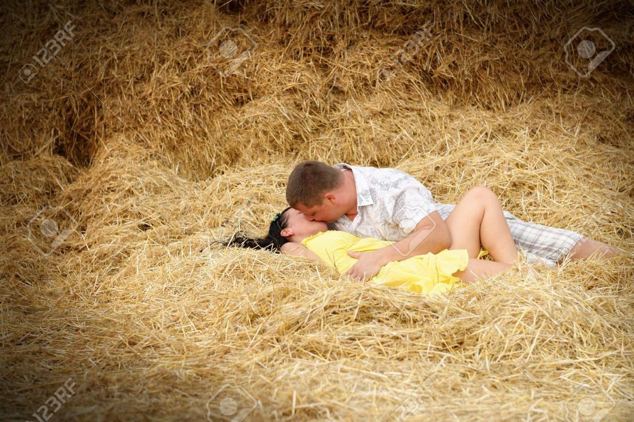 A couple in kissing at hay. Adult man and woman lie on the fresh hay Stock Photo - 14649522