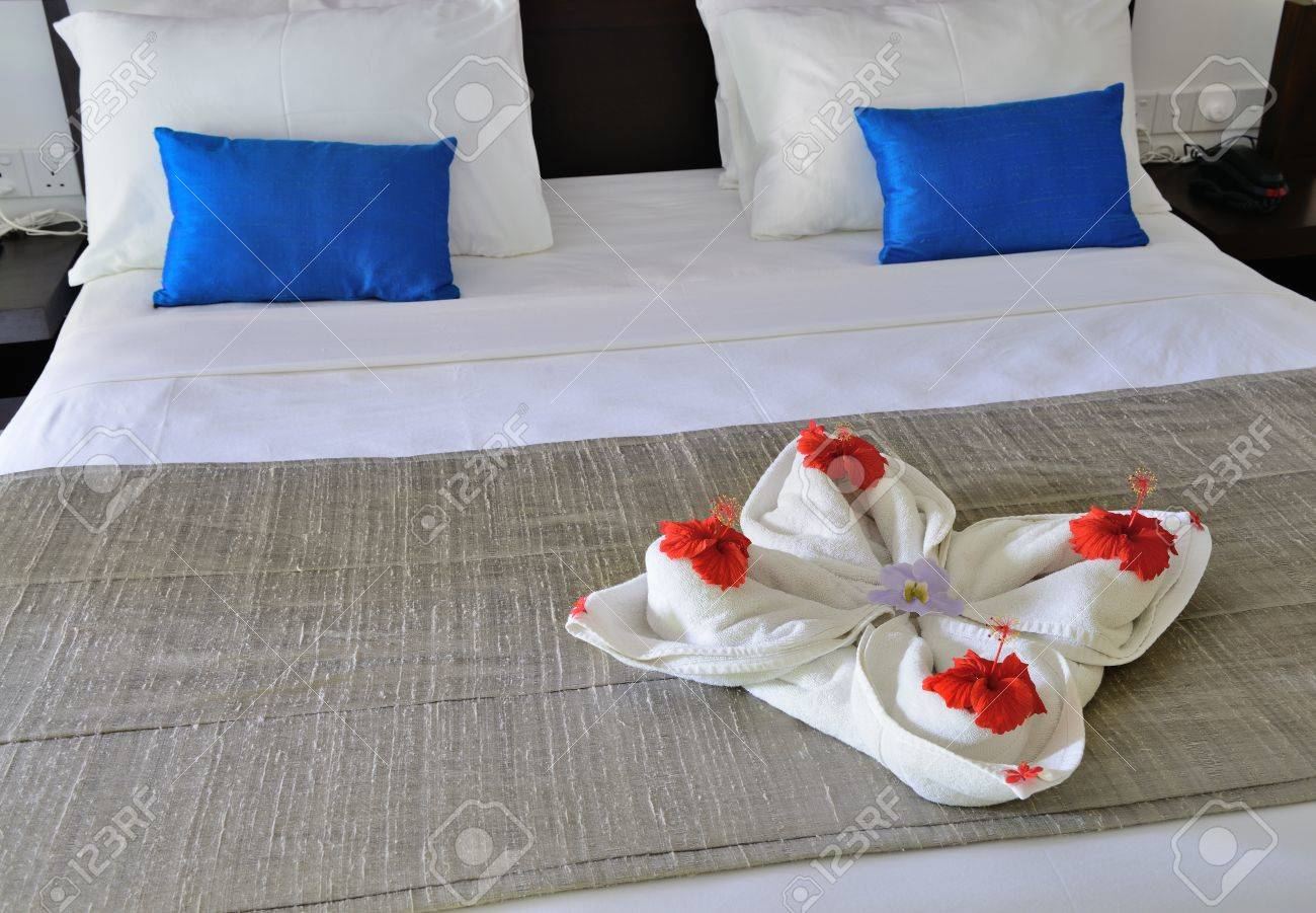 room in a hotel with a decoration of the towel and flowers on