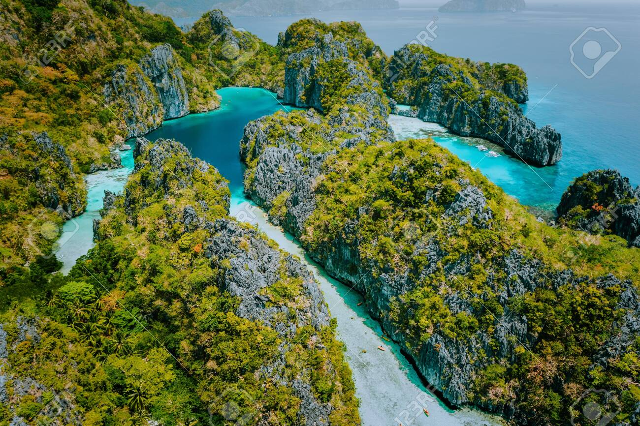 Aerial drone view beautiful shallow tropical Big and Small Lagoon explored inside by tourist on kayaks surrounded by jagged limestone karst cliffs. El Nido, Palawan Philippines - 125523314