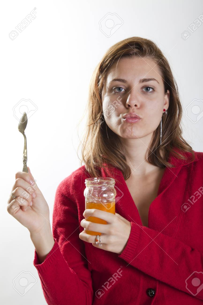 young woman holding a jar of honey and a spoon in her hands looking sexy Stock Photo - 15784570