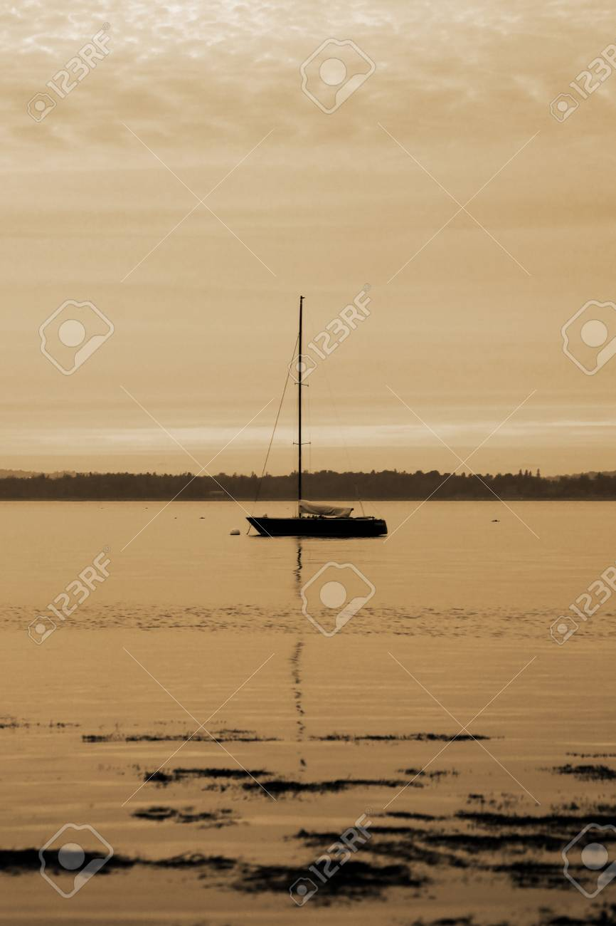 sepia toned boat alone off shore at sunset Stock Photo - 17347149