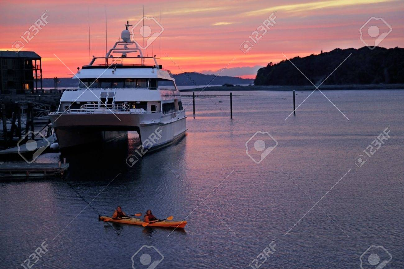 large boat in a harbour at sunset with people in kayak near it Stock Photo - 17365352