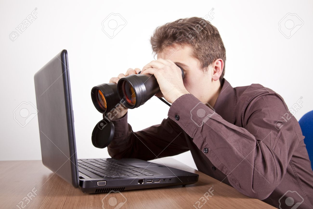 Young Man Searching On The Web At A Laptop With Binoculars Stock ...