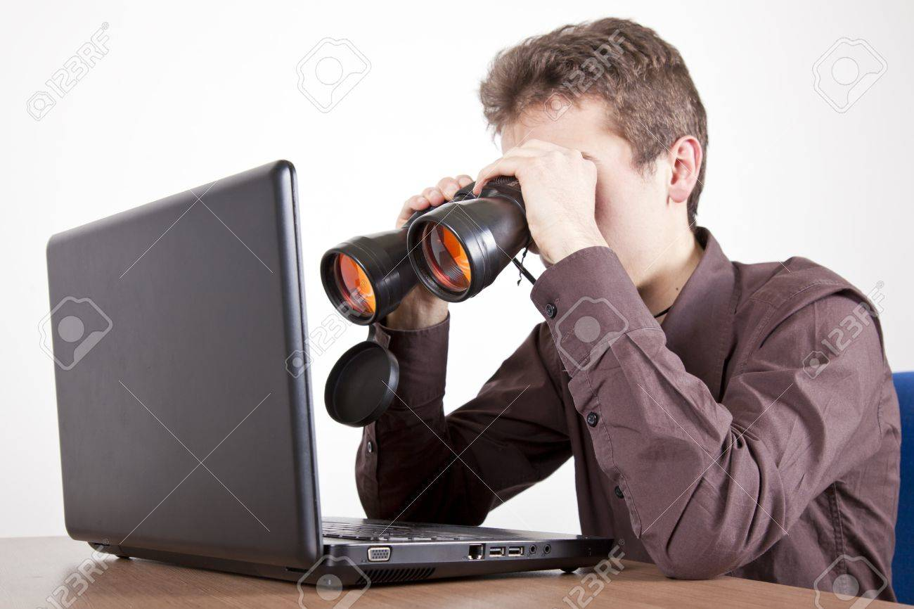 Man Searching On At A Desk With Binoculars On A Computer Screen ...