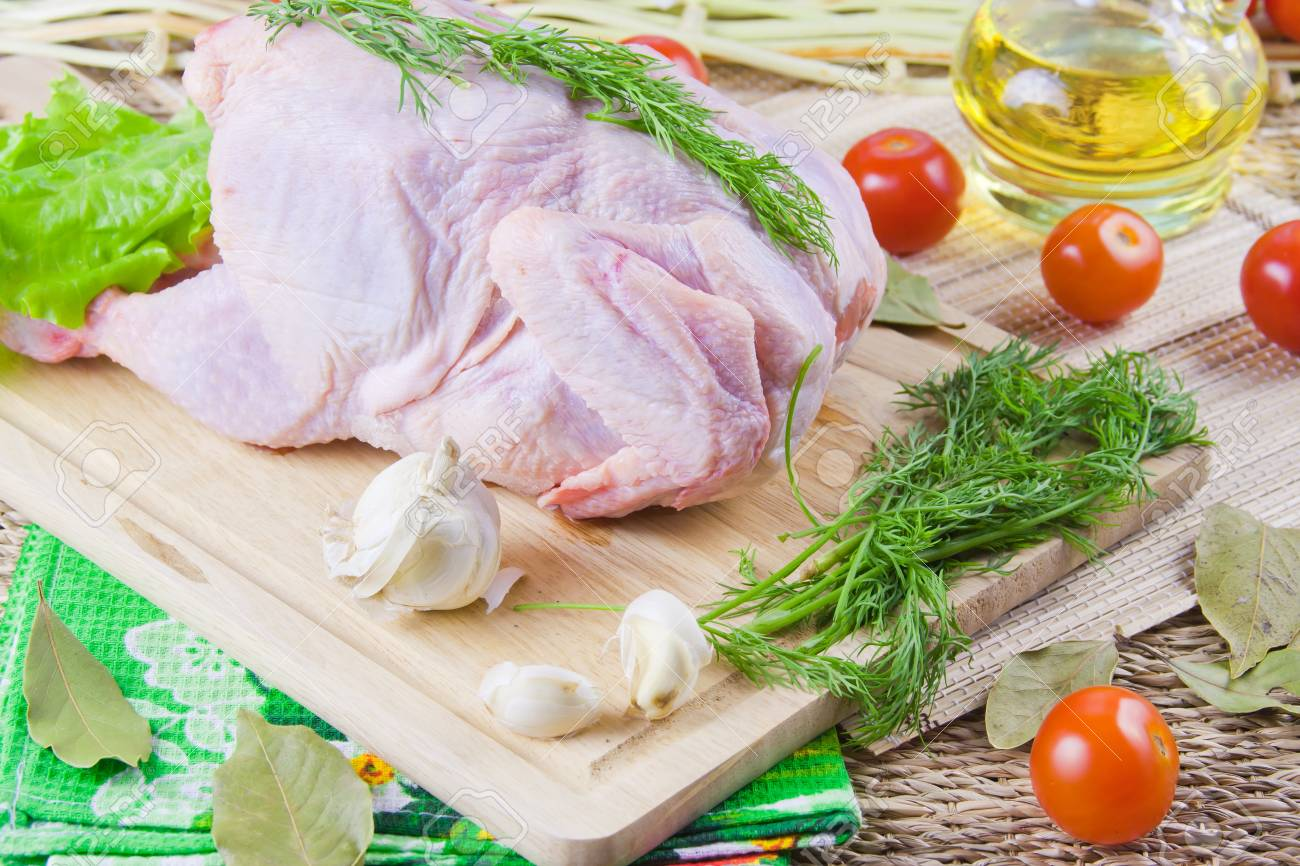 chicken carcass on a wooden board with tomatoes and fresh greenery Stock Photo - 16714629