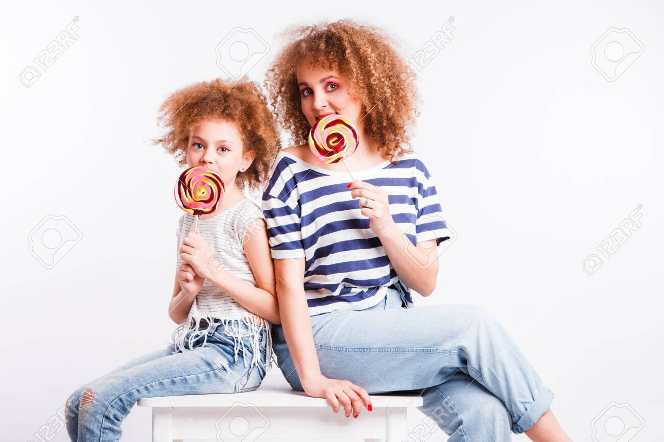 Mom and daughter with natural small curls on the head with bright