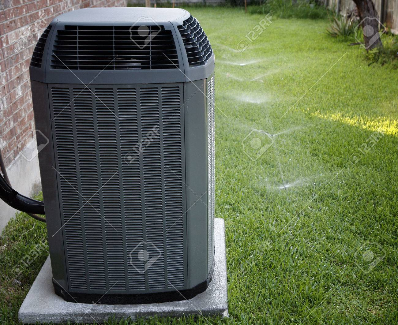 Modern air conditioner on backyard with working sprinkler system - 37539909